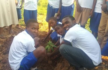 Image of WDGO worker planting a tree at Nzove School with eager environmental students.